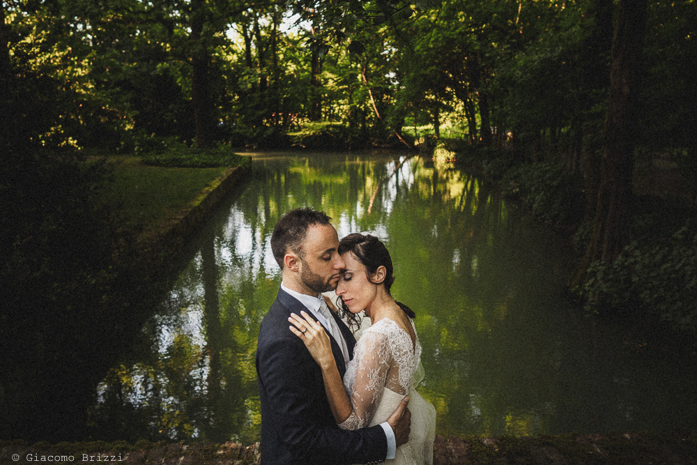 Abbraccio tra gli sposi con sfondo il laghetto matrimonio Castello di Paderna a Pontenure