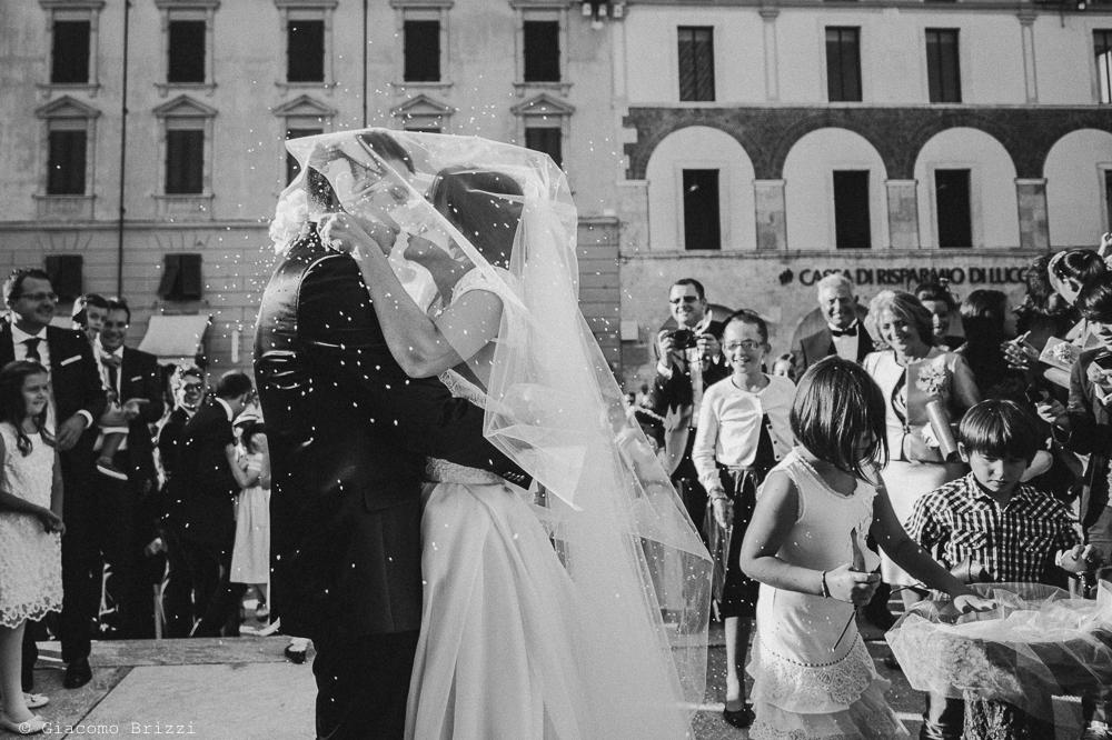 Bacio tra gli sposi fuori la chiesa, fotografo matrimonio ricevimento villa fanini, Lucca