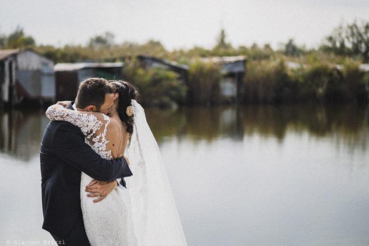 Un appassionato abbraccio degli sposi in riva al laghetto al matrimonio valle di badia