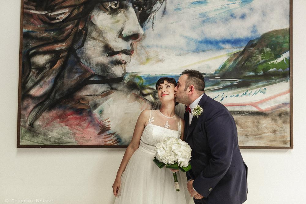 Sposo bacia la sposa con quadro sullo sfondo, matrimonio Massa Carrara Toscana